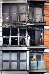 © Licensed to London News Pictures. 07/05/2021. London, UK. A fire fighter stands on a balcony below the charred remains of apartments at New Providence Wharf in Poplar in east London. 100 fire fighters and 20 crews tackled the blaze at it's peak. Photo credit: Peter Macdiarmid/LNP