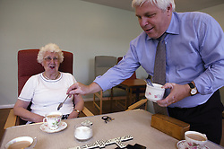 Care worker putting sugar into elderly woman's cup of tea at day centre,