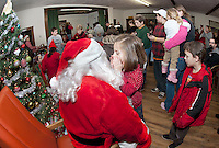 Kennedy Reardon whispers into Santa's ear what she would like for Christmas this year at the Wicwas Grange Christmas gathering with family and friends.  (Karen Bobotas/for the Laconia Daily Sun)