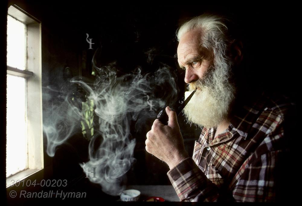 Sveinbjorn Beinteinsson, priest of 80-man Norse pagan religion, smokes pipe beside window inside Iceland