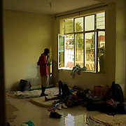 """A burundian university student, seeking shelter outside the US embassy in Bujumbura, talk to a college recovering from malaria, in a room of a vacant building close by. The students moved to the area in early May because, they claim, the US authorities ensure their security, after their university was closed amid anti-government protests. The government closed the university at the end of April, citing """"insecurity""""."""