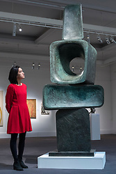 """© Licensed to London News Pictures. 18/11/2016. London, UK. A staff member views """"Parent I"""" by Dame Barbara Hepworth (est. GBP2-3m), at the preview at Sotheby's of works on view at four upcoming November auctions featuring Modern & Post-War British Art, A Painter's Paradise (Julian Trevelyan & Mary Fedden at Durham Wharf), Scottish Art and Picasso Ceramics from the Lord & Lady Attenborough Private Collection. Photo credit : Stephen Chung/LNP"""
