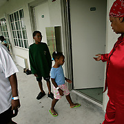 """PALM BEACH, LA - September 6, 2005: .Families and their children at the Palm Meadows complex in West Palm Beach, Florida on September 6, 2005...The Johnson Family:  Father is Kevin Johnson, 38, wife is Michelle Johnson, 27, daughter My-Shelle, 8, son Kevin the 3rd (nickname """"Ope""""), 7, son Kevin the 4th (nicknamed """"Old Man""""), 5, Kevin the 5th (Nickname """"Little Kevin""""), 2 and baby in stroller is I-Shelle, 7 months. The family is walking and playing a game called Under the Bridge.....Family outside their room is Rosa Angelatta, her daughter Sandra Smith (in red) and her grandson, Kenneth, 11, playing with Sandra's niece, Eleanora, 5...Girl with large Tweety Bird doll: Chelsea Gair, 7, walking to her room with stuffed Tweety Bird. They evacuated from New Orleans."""