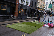 At the six-month point of England's Coronavirus pandemic lockdown, restaurant workers prepare the street outside their business, where table places are to be set for their customers who will be eating al fresco in Bateman Street, on 24th September, in London, England. New restrictions are being re-introduced by the government after a sudden climb in the Covid infection rate, a predicted 'second spike'.