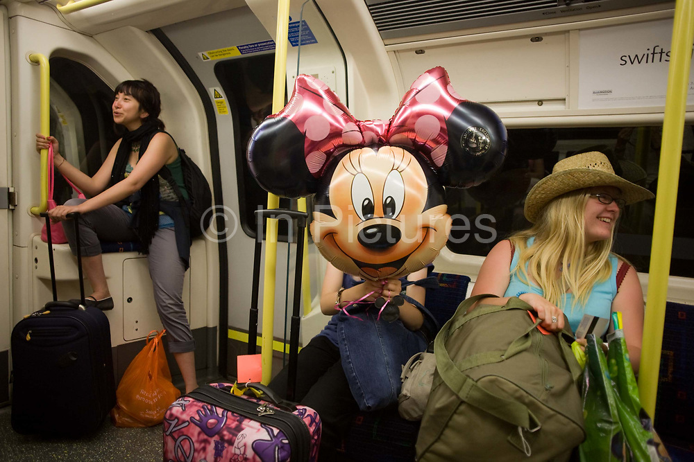 A Minnie Mouse balloon brought from Disneyworld, Paris, is carried on a London Underground tube train. The face of Minnie obscures the young girl's own features but to her right is a friend who has also returned to their home city after some time enjoying the Disney theme park in the French capital. Another train passenger seems amused by the cartoon character's presence in these otherwise drab surroundings - Minnies' smile to the camera makes for a humorous moment for these commuters under the streets of London.
