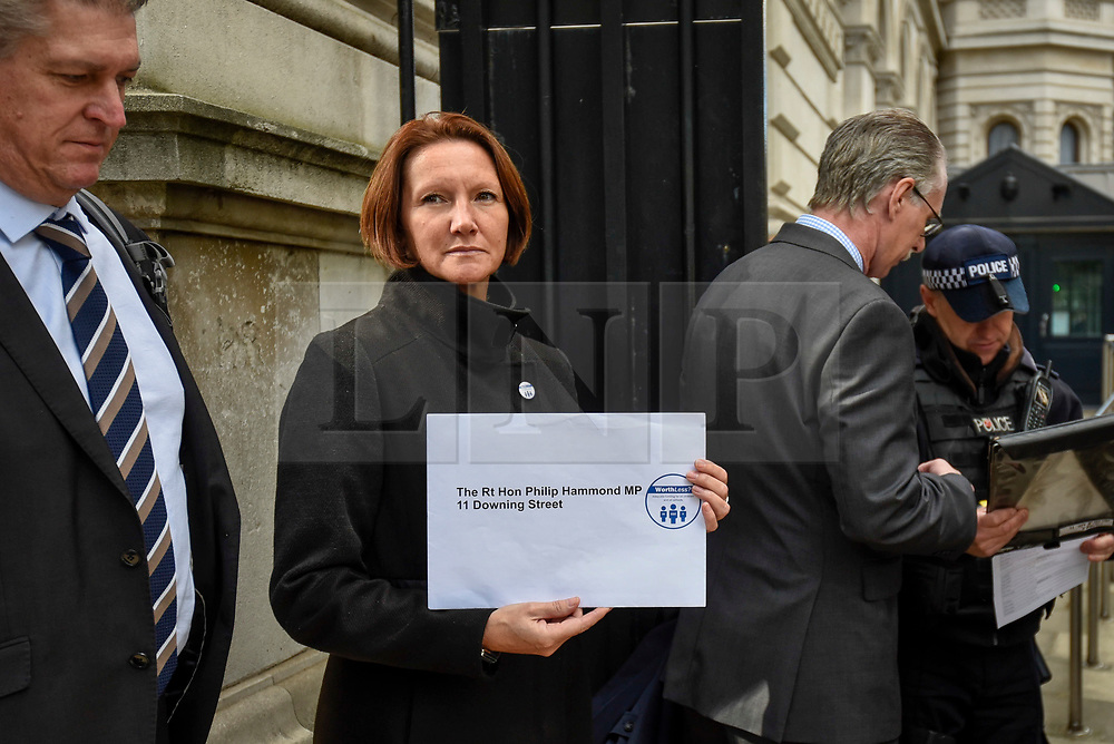© Licensed to London News Pictures. 28/09/2018. LONDON, UK.  One of a group of six head teachers stands outside the entrance to Downing Street with a petition to be delivered to Number 11 Downing Street after hundreds of head teachers gathered at a rally in Parliament Square to demand extra funding for schools.  With a reported reduction in per student funding in real terms since 2010, members of the National Union of Head Teachers and the Association of School and College Leaders attending the rally also warn of increasing class sizes, staff cuts, and reduced subject choice.  Photo credit: Stephen Chung/LNP