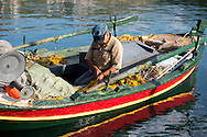 A fisherman working on his nets in a colourful old boat in Gaios harbour on Paxos, The Ionian Islands, The Greek Islands, Greece, Europe