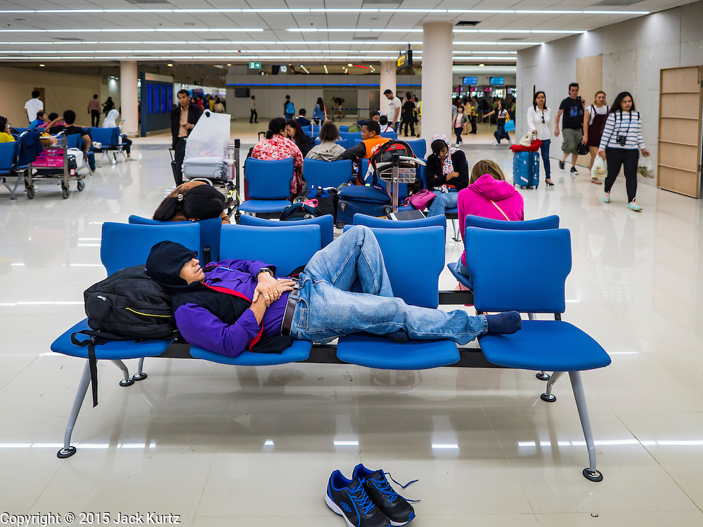 """24 DECEMBER 2015 - BANGKOK, THAILAND:  A passenger sleeps in the new domestic terminal at Don Muang (also spelled Don Mueang) International Airport. The new terminal had its """"soft"""" opening Dec. 24. Don Muang is the airport used by low cost airlines serving Bangkok and is now the largest airport in the world for low cost carriers. In 2014, more than 21million passengers used Don Muang. Don Muang International Airport is the oldest airport in Asia and one of the oldest airports in the world. It started functioning as an airfield in 1914.    PHOTO BY JACK KURTZ"""
