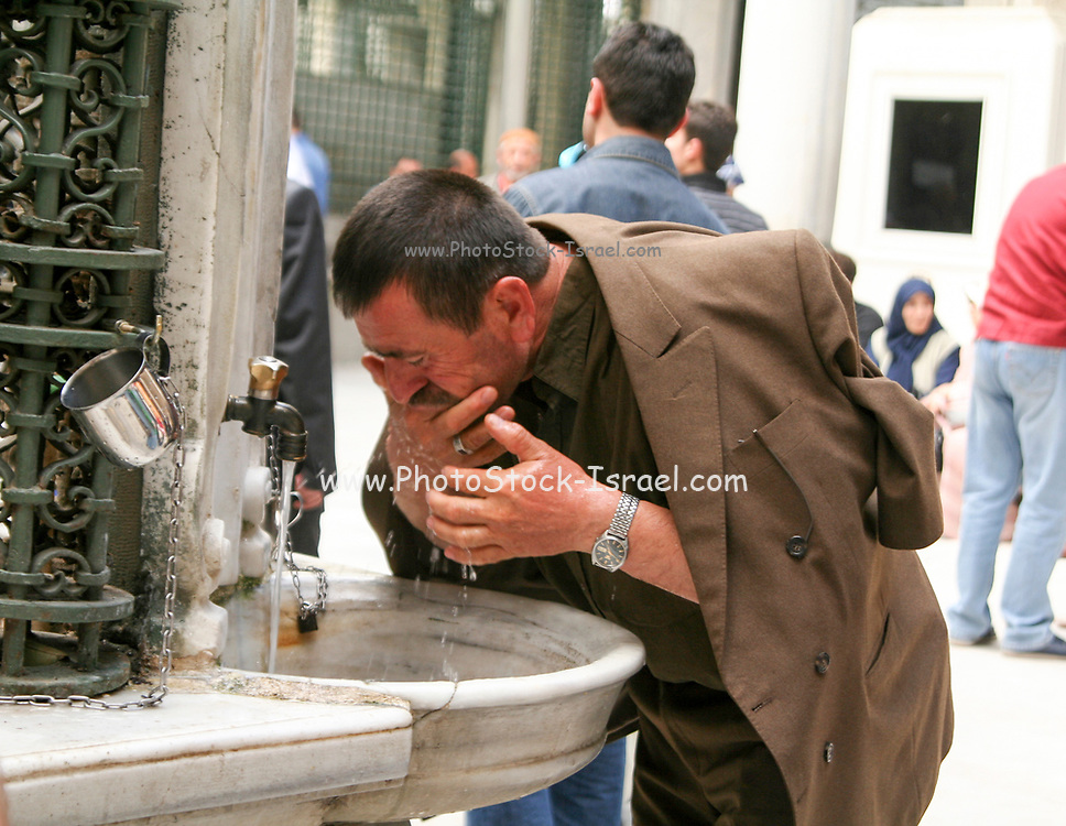 Turkish man washes his feet before entering a mosque to pray