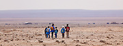 "Syrian Bedouin school children return to their tents near Qasr al-Hayr al-Sharqi (Eastern al-Hayr Palace or the ""Eastern Castle"") a castle in the middle of the Syrian Desert"