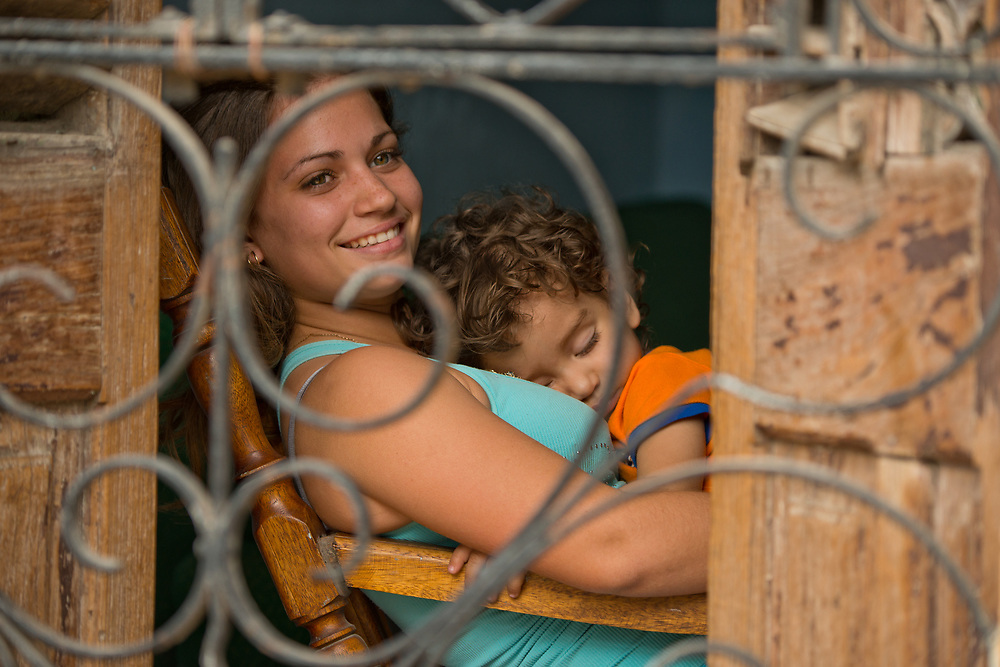 Young woman rocking a sleeping child in chari in wondow of Old Havana, Cuba Cuba