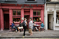 Two women chatting outside of Mildreds Cafe, London, England