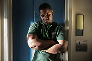 A young male prisoner standing outside a cell door. HMP/YOI Portland, Dorset., United Kingdom.