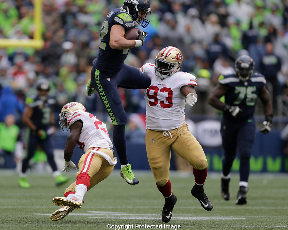 In this fourth in a series of seven photos, Seattle Seahawks tight end Luke Willson leaps over San Francisco 49ers cornerback Will Redmond, left, as defensive tackle D.J. Jones (93) moves in to tackle in the first half of an NFL football game, Sept. 17, 2017, in Seattle. (AP Photo/John Froschauer)