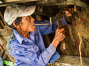 04 NOVEMBER 2015 - YANGON, MYANMAR:  A worker repairs the hull of a small wooden ferry on the banks of the Yangon River in Dala. Dala is located on the southern bank of Yangon River across from downtown Yangon, Myanmar. Many Burmese live in Dala and surrounding communities and go across the river into central Yangon for work. Before World War 2, the Irrawaddy Flotilla Company had its main shipyards in Dala. That tradition lives on in the small repair businesses the work on the hundreds of small wooden boats that serve as commuter ferries for the people of Yangon. The boats are pulled up onto the riverbank in Dala and repaired by hand.   PHOTO BY JACK KURTZ