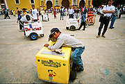 FEB 24, 2001 - SAN CRISTOBAL DE LAS CASAS, CHIAPAS, MEXICO: Ice cream vendors on the Zocalo in San Cristobal de las Casas, Chiapas, Mexico. Many children are forced to work as vendors because their parents are not able to support them with the jobs they might have.  © Jack Kurtz    CHILDREN  CHILD LABOUR  CROWDS   ECONOMY   FOOD   POVERTY  TOURISM  UNEMPLOYMENT