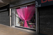Pink curtain in the window of a closed hair dressers as the third national coronavirus lockdown continues, during the first days of the easing of lockdown restrictions on 30th March 2021 in Birmingham, United Kingdom. After months of lockdown, the first signs that life will start to get back to normal begin, with more people enjoying the company of others in public, as the rule of six starts the first stage of lockdown ending.