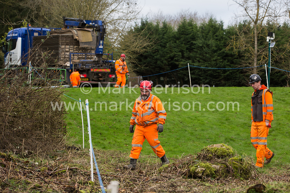 Denham, UK. 4 February, 2020. Engineers walk across land cleared for works for the HS2 high-speed rail link project. Behind other engineers prepare to unload a temporary roadway from a large truck. Planned works in the immediate vicinity are believed to include the felling of 200 trees and the construction of a roadway, Bailey bridge, compounds, fencing and a parking area.
