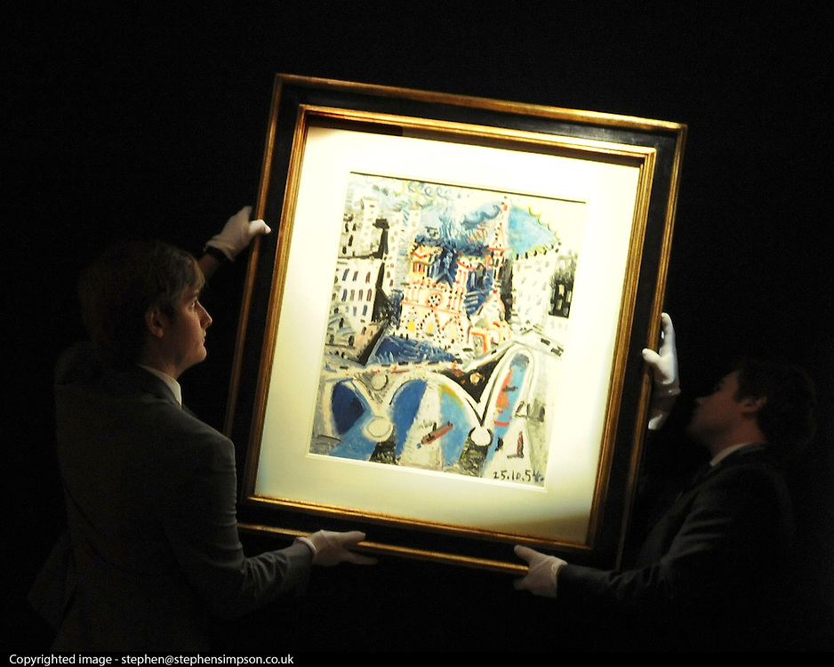 © Licensed to London News Pictures. 02/02/2012, London, UK. Two gallery assistants hang 'Notre `dame de `paris by Pablo Picasso. The painting is expected to raise 700,000 - 1,000,000GBP. Photo call at Bonhams, London for Impressionist and Modern Art Auction preview..  Photo credit : Stephen Simpson/LNP