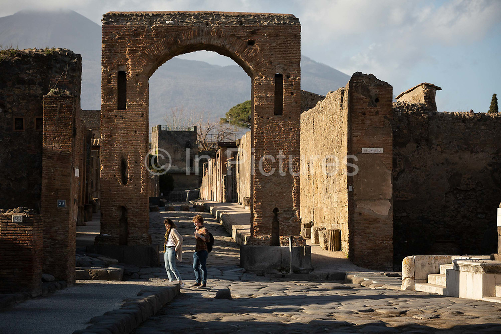 Peeople walk in front of an arch in the Pompeii Archeological Park on Friday 6th March 2020 in Pompei, Italy. Park officials estimate that visitor numbers are down to a sixth of what they would normally be as a result of the spread of Coronavirus, which has prompted the closure of all Italian schools and universities, and the postponing of many sporting events. .