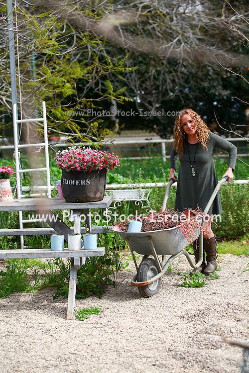 Woman works in her garden arranging flowers in a flowerpot