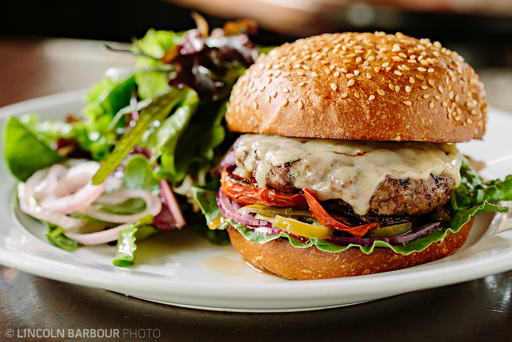 A close up view of a mouth watering burger adorned with cheese and pickled vegetables, served with a side salad.