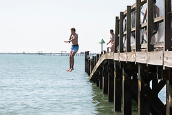 © Licensed to London News Pictures. 31/07/2020. Southend, UK. A young man jumps into the water of Southend-on-Sea beach as social distancing measures are relaxed and temperatures are expected to be over 30c. British holiday makers have chosen to book staycations in the UK as the uncertainty of Covid-19 lockdown looms. Photo credit: Ray Tang/LNP