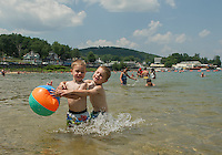 Brenden and David Money visiting from Ashburnham, MA are having a ball together as they cool off in the water at Weirs Beach on Wednesday afternoon.  (Karen Bobotas/for the Laconia Daily Sun)