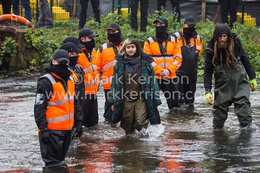 Denham, UK. 5th November, 2020. HS2 security guards monitor anti-HS2 activists wading in the river Colne at Denham Ford in order to try to delay bridge building works for the HS2 high-speed rail link on the first day of the second national coronavirus lockdown. Prime Minister Boris Johnson has advised that construction work may continue during the second lockdown but those working on construction projects are required to adhere to Site Operating Procedures including social distancing guidelines to help prevent the spread of COVID-19.