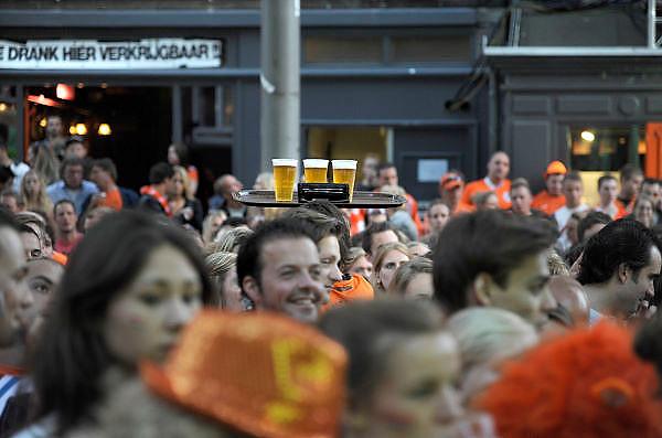 Nederland, Nijmegen, 17-6-2012Voetbalfans, oranjefans, mensen kijken op het koningsplein via een groot beeldscherm naar de ek wedstrijd van oranje tegen portugal. Nederland opende de score, maar was aan het eind van de wedstrijd verslagen en uitgeschakeld. Obers bezorgen de bestelling van bier.Foto: Flip Franssen/Hollandse Hoogte