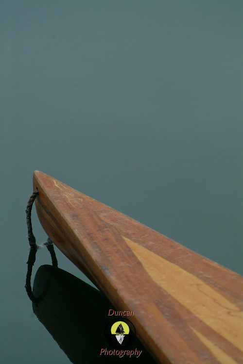 a wooden kayak rests in a calm corner of the harbor at Buck's Harbor Maine