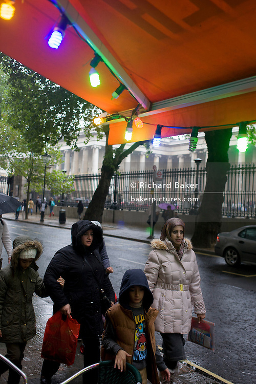 A family walk beneath coloured lights during damp, gloomy weather in central London.