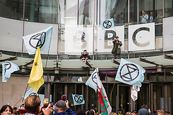 London, UK. 11 October, 2019. BBC staff including Rory Cellan-Jones, observe climate activists from Extinction Rebellion, two of which standing on a glass parapet, blocking the main entrance to the BBC's New Broadcasting House on the fifth day of International Rebellion protests. They were demanding that the broadcaster 'tell the truth' regarding the climate emergency.