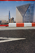 A construction hoarding showing London's Shard skyscraper and Give Way triangle at a road junction in south London. As a visual rhyme, we see the echoes of shapes and geometry, a repeating of triangles and diagonals - a geometric shape and a skyscraper with scale and perspective. Standing 306 metres (1,004 ft) high, the Shard is currently the tallest building in the European Union, by Italian architect Renzo Piano that dominates this borough of Southwark in south London.