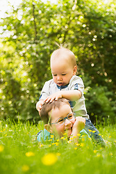 Small boy sitting on his brother in the garden