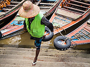 22 OCTOBER 2015 - YANGON, MYANMAR: A man who operates a cross river ferry in Yangon jumps off his boat on the Yangon side of the river.     PHOTO BY JACK KURTZ