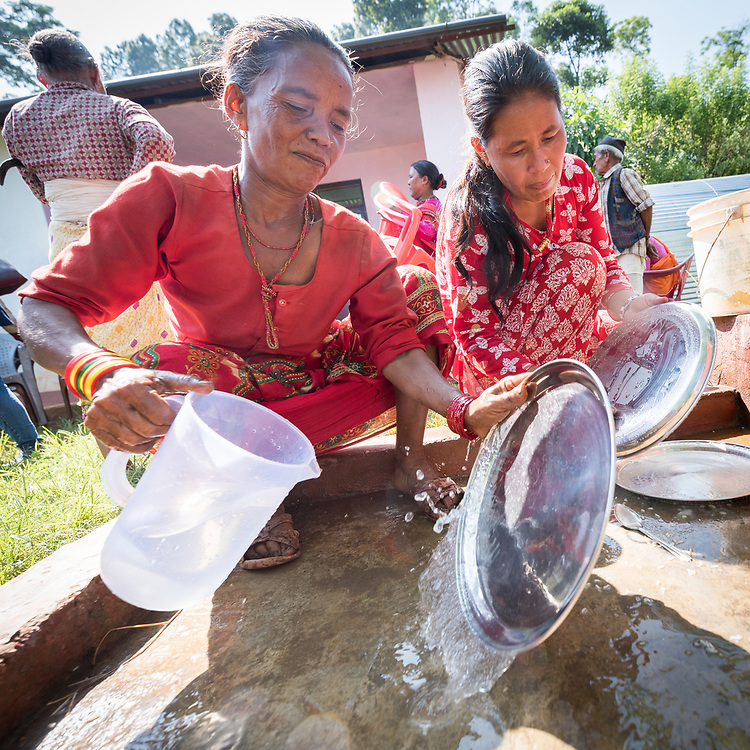 17 September 2018, Biruwa, Kavre district, Nepal: Women clean the dishes after lunch in the village of Biruwa. What may have appeared an ordinary lunch was in fact quite special. As Dalits find themselves among the most marginalized in Nepal society, members of other castes will often not receive food from them even if offered. Today, however, a range of visitors, including local authority officials sit and eat with them, to affirm the equality and dignity of all people, no matter their ethnic group, economic situation, or caste. The Lutheran World Federation World Service programme runs a Post-Earthquake Rehabilitation and Livelihood Recovery Project, in which Biruwa is one of the supported communities.