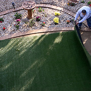 Synlawn employee Jaime Moreno installs turf in the backyard of Glendale resident E. Normand Blanchette.