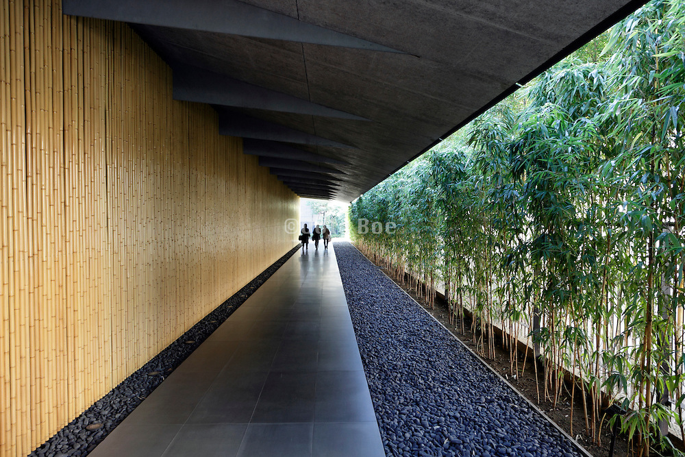 three people at the end of a long entrance corridor at The Nezu Museum building Tokyo Japan
