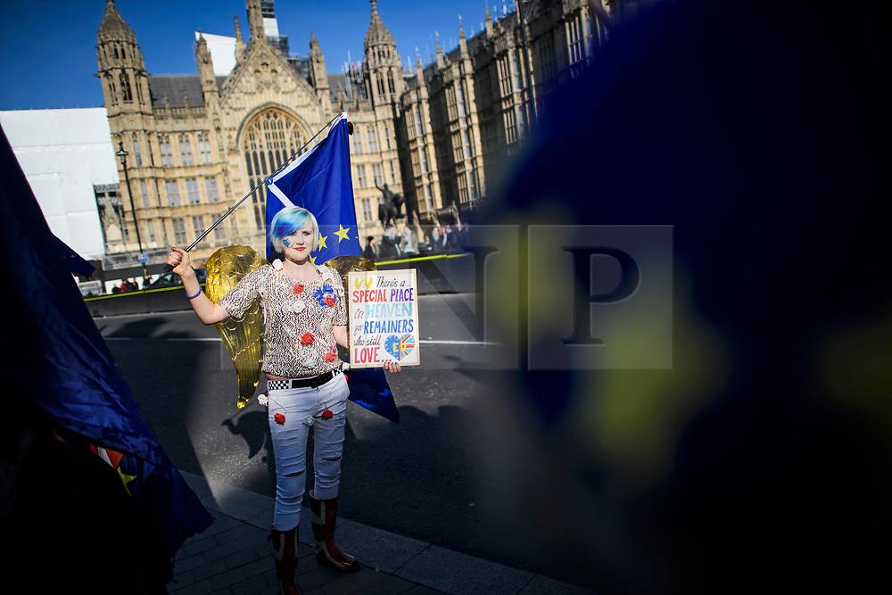 """© Licensed to London News Pictures. 14/02/2019. London, UK. Self titled """"EU Supergirl, an Anti Brexit campaigner, outside the Houses of Parliament in Westminster, on the day that MPs are due to take part in further debates and votes on Brexit. A series of amendments are being tabled to try to change the direction of Brexit, but a vote on a deal will not be held today as was originally planned. Photo credit: Ben Cawthra/LNP"""