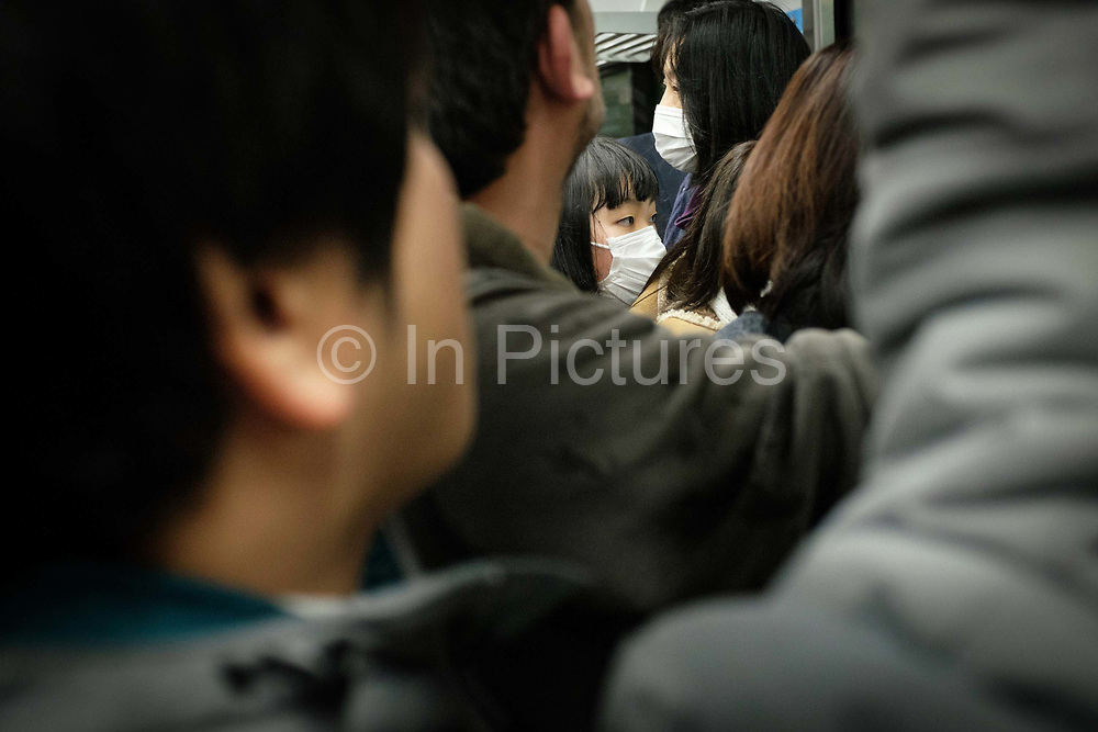 Commuters on the Tokyo subway. The combined subway network of the Tokyo and Toei metros comprises 290 stations and 13 lines. Some 8.7 million passengers travel on the subway each day. Japan.