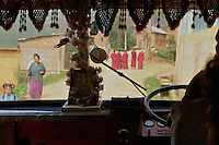 Travelling through a village, on a typically decorated bus in the Kathmandu Valley.