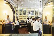 Employees works behind the counter at Fábrica dos Pastéis de Belém, in Lisbon.