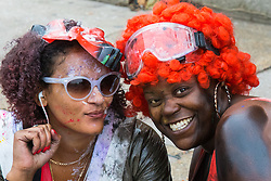 London, August 30th 2015. Two women, already smeared in paint pose for the camera as revellers await the start of the Notting Hill Carnival.