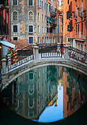 "One of many foot bridges in Venice, reflecting in a small canal<br /> .....<br /> Venice is a city in northeastern Italy sited on a group of 118 small islands separated by canals and linked by bridges. It is located in the marshy Venetian Lagoon which stretches along the shoreline, between the mouths of the Po and the Piave Rivers. Venice is renowned for the beauty of its setting, its architecture and its artworks. The city in its entirety is listed as a World Heritage Site, along with its lagoon. Venice is the capital of the Veneto region. In 2009, there were 270,098 people residing in Venice's comune. Although there are no historical records that deal directly with the founding of Venice, tradition and the available evidence have led several historians to agree that the original population of Venice consisted of refugees from Roman cities near Venice such as Padua, Aquileia, Treviso, Altino and Concordia (modern Portogruaro) and from the undefended countryside, who were fleeing successive waves of Germanic and Hun invasions. Some late Roman sources reveal the existence of fishermen on the islands in the original marshy lagoons. They were referred to as incolae lacunae (""lagoon dwellers""). The traditional founding is identified with the dedication of the first church, that of San Giacomo at the islet of Rialto (Rivoalto, ""High Shore""), which is said to have been at the stroke of noon on 25 March 421."
