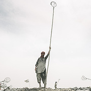 Local Muslim men stand on the rim with nets attached to long poles and try to be the first one to catch the coconuts that have been thrown in the cold mud by pilgrims. They collect the coconuts and will either sell them back to newcomer pilgrims, resale it in the market or keep it for themselves.