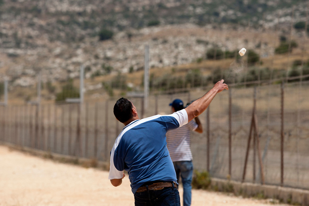 A Palestinian man hurls a stone towards Israeli troops (not seen), during a protest against Israel's separation barrier in the West Bank village of Beit Nuba on June 04, 2010.
