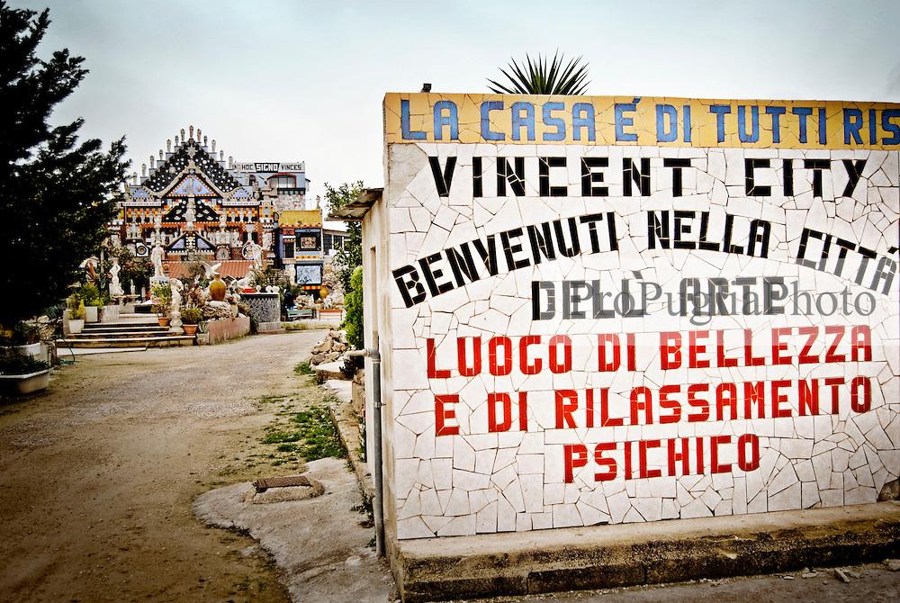 """L'ingresso di """"Vincent City"""", residenza del pittore salentino """"Vincent Brunetti"""" nei pressi di Guagnano in provincia di Lecce. 29/03/2009 (PH Gabriele Spedicato) ..VINCENT BRUNETTI.Affettuosamente identificato con l'appellativo """"LA LIBELLULA DEL SUD"""", Vincent Brunetti è oggi considerato uno dei personaggi più emblematici della vita artistica meridionale..Nato a Guagnano di Lecce il 3 dicembre 1950 e residente a Milano da oltre vent'anni dove per i meriti artistici (egli è infatti pittore e scultore) gli è stato conferito nel 1970 l'AMBROGINO D'ORO. Fu colpito in tenera età dal virus della poliomelite. Gli effetti devastanti della malattia a seguito di due delicati interventi al piede sinistro lo stavano portando ad una quasi totale immobilità..Comincia comunque a dipingere e consegue, con il massimo dei voti, il diploma alla Scuola d'arte di Lecce..Dopo essere stato a Torino, si trasferisce a soli venticinque anni a Milano dove riceve numerosi riconoscimenti ed entra in contatto con elementi di spicco della scena artistica milanese come Francesco Messina (sotto la cui guida frequenta l'Accademia di Brera); Giacomo Manzù che lo segue ed incoraggia nel corso della sua attività; Arnaldo Pomodoro che lo accoglie presso la sua Bottega..Sempre a Milano, egli collabora con l'attrice Paola Borboni ed il poeta Bruno Villar alla realizzazione di numerose attività culturali e di diversi programmi televisivi..Con il passare degli anni egli è sempre più debilitato dalla malattia..Grazie alla geniale scoperta di Mariano Orrico, ideatore """"Lamina Bior"""" secondo il quale, ogni genere di malattia può essere sconfitta con il proncipio dell'elettricità statica, Vincent Brunetti ha potuto recuperare in pieno la sua vitalità e gioia di vivere..Nella sua """"DANZA"""" propiziatoria è espresso in pieno il bisogno di LIBERTA' che è nascosto nel cuore di ogni uomo e nel suo """"VOLO"""" il desiderio di liberarsi dal peso della materia..Nell'elasticità delle articolazioni rese forte e robuste da un ormai"""