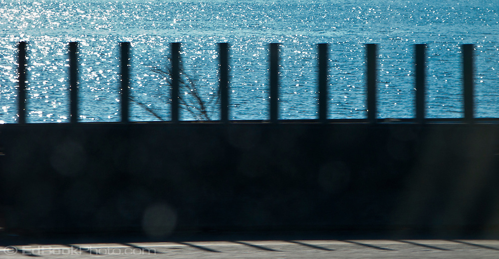 abstracted by motion blur a highway barrier with a tree branch and blue seawater beyond panorama