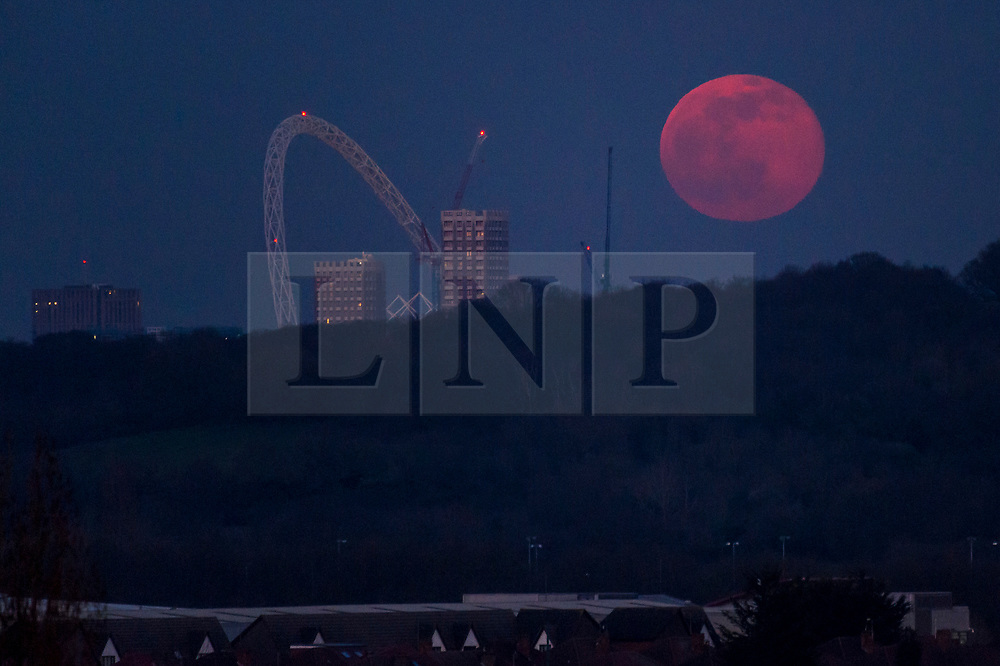 © Licensed to London News Pictures. 27/02/2021. LONDON, UK. The full snow moon rises near Wembley Stadium. This month's full moon according to the Old Farmer's Almanac, has the name Snow Moon due to the typically heavy snowfall that occurs in February. Photo credit: Stephen Chung/LNP